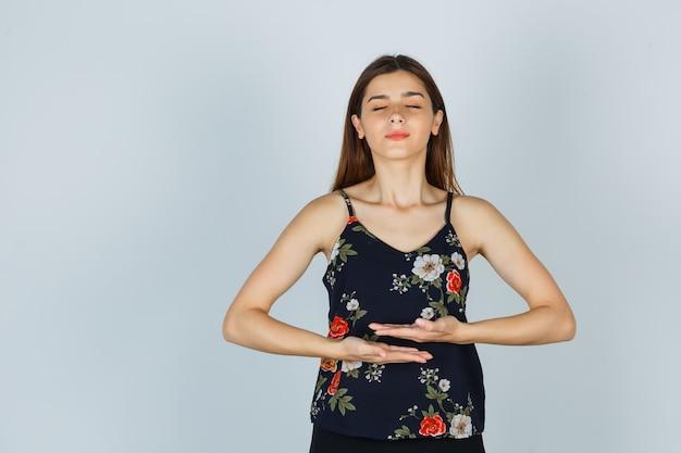 Młoda dama robi medytację z zamkniętymi oczami w bluzce i wygląda na spokojną. przedni widok.