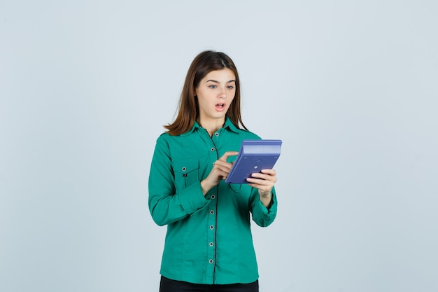 Młoda dama robi obliczenia na kalkulatorze w zielonej koszuli i wygląda na zdumioną. przedni widok.