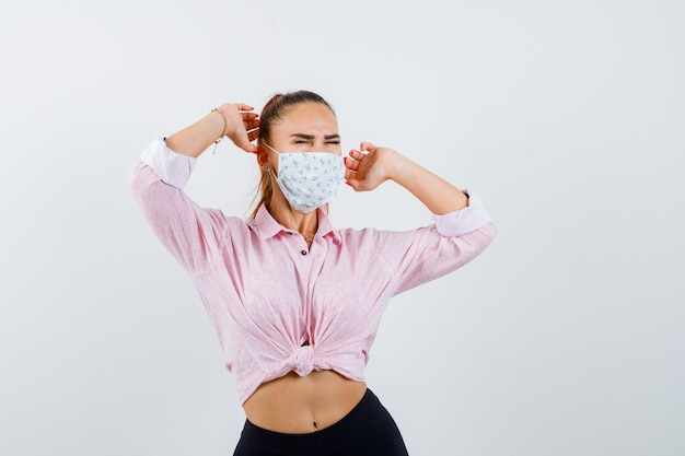 Młoda dama rozciąga górną część ciała w koszuli, masce i wygląda na zrelaksowaną. przedni widok.