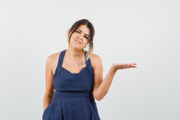 Młoda dama rozkłada dłoń w sukience i wygląda pewnie