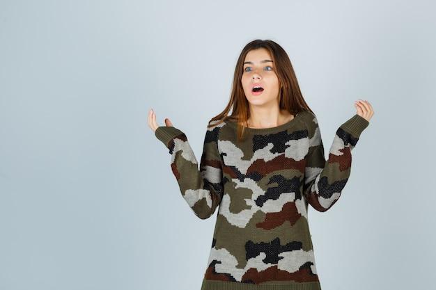 Młoda dama rozkłada dłonie w swetrze i wygląda na zakłopotaną