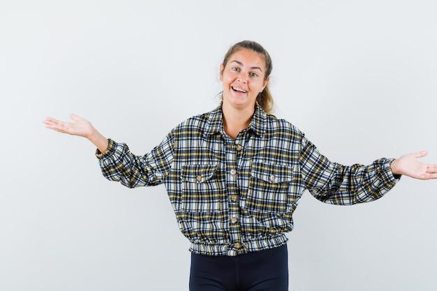 Młoda dama rozkłada ręce w koszuli, szortach i wygląda na szczęśliwą. przedni widok.