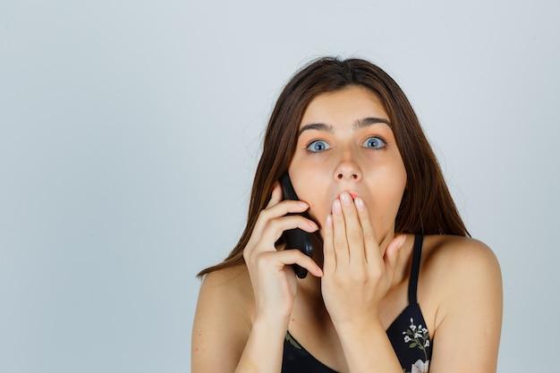 Młoda dama rozmawia na smartfonie, trzymając rękę na ustach w bluzce i patrząc w szoku. przedni widok.
