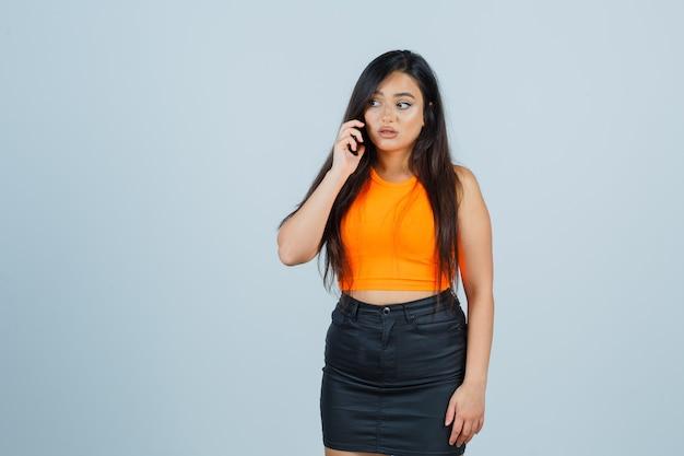 Młoda dama rozmawia przez telefon komórkowy w podkoszulku, mini spódniczce i wygląda zdziwiona, widok z przodu.