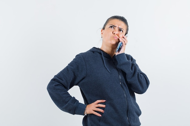Młoda dama rozmawia przez telefon myśląc w kurtce i patrząc zdziwiony. przedni widok.