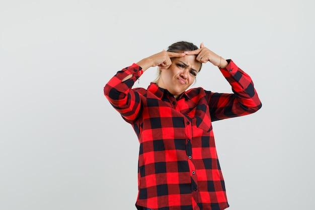 Młoda dama ściskająca pryszcz na czole w koszuli w kratę