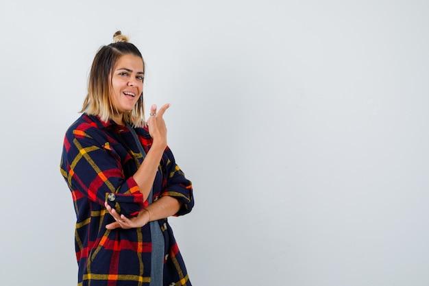 Młoda dama skierowana w górę, stojąca bokiem w casualowej koszuli w kratę i wyglądająca na szczęśliwą.