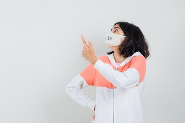 Młoda dama skierowana w górę w bluzie z kapturem, maska na twarz