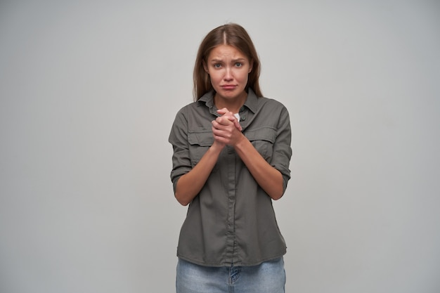 Młoda dama, śliczna kobieta z brązowymi długimi włosami. ubrana w szarą koszulę i dżinsy. trzymaj ręce razem i błagaj. oglądając zdenerwowany aparat na białym tle na szarym tle
