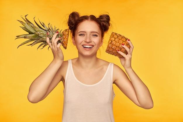 Młoda dama, śliczna ruda kobieta z dwiema bułeczkami. ubrana w białą koszulę i trzymająca wycięty ananas obok twarzy z szerokim uśmiechem, zdrowy styl życia. oglądanie na białym tle nad żółtą ścianą