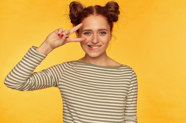 Młoda dama, śliczna, wesoła ruda kobieta z dwiema bułeczkami. ubrana w sweter w paski i pokazująca znak pokoju na oku, przygryza wargę. oglądanie na białym tle nad żółtą ścianą