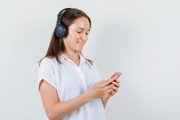 Młoda dama słucha muzyki, patrząc na swój telefon w białej bluzce i patrząc wesoło.