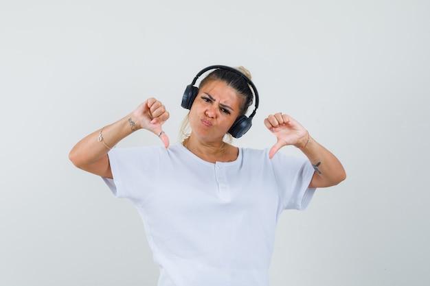 Młoda dama słuchająca muzyki, pokazująca podwójne kciuki w dół w koszulce, widok z przodu.