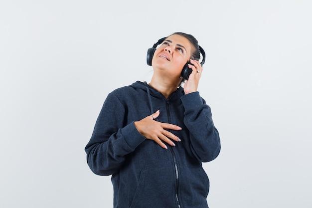 Młoda dama słuchająca muzyki w kurtce i patrząc skoncentrowana. przedni widok.