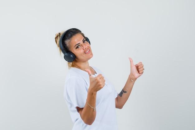 Młoda dama słuchania muzyki, pokazując podwójne kciuki w widoku z przodu t-shirt.