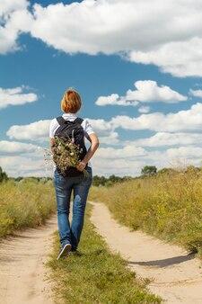 Młoda dama spaceru na wiejskiej drodze. turysta z plecakiem spacerujący na świeżym powietrzu w naturze. podróżnik spacerujący szlakiem na świeżym powietrzu. zdrowy aktywny styl życia