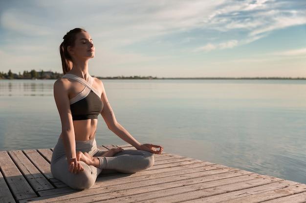 Młoda dama sportowa na plaży wykonuje ćwiczenia medytacyjne.