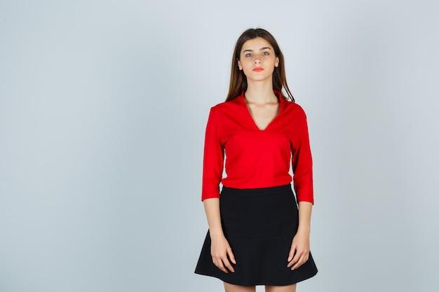 Młoda dama stoi prosto, pozując przy aparacie w czerwonej bluzce