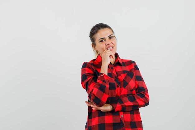 Młoda dama stoi w myślącej pozie w kraciastej koszuli i wygląda rozsądnie