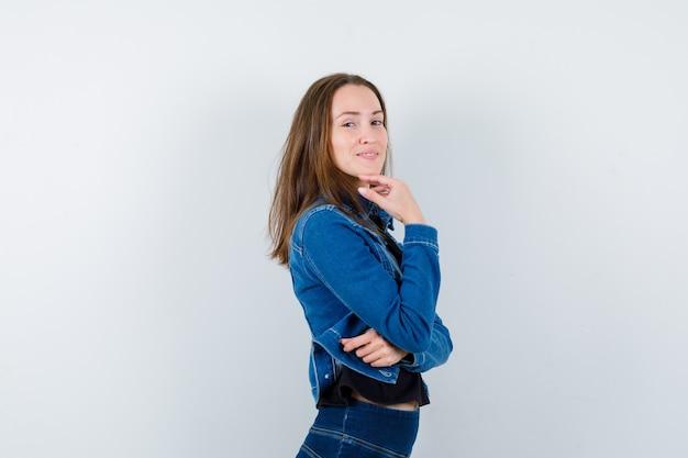 Młoda dama stoi w pozie myślenia w bluzce i wygląda ładnie.