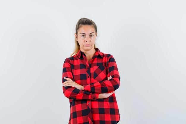 Młoda dama stoi ze skrzyżowanymi rękami w koszuli w kratkę i wygląda pewnie