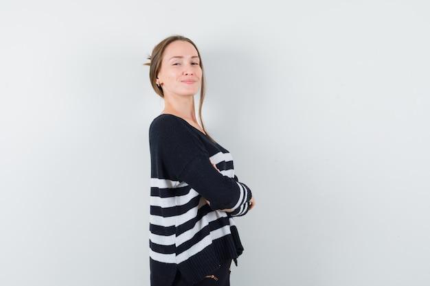 Młoda dama stoi ze skrzyżowanymi rękami w swobodnej koszuli i wygląda dumnie