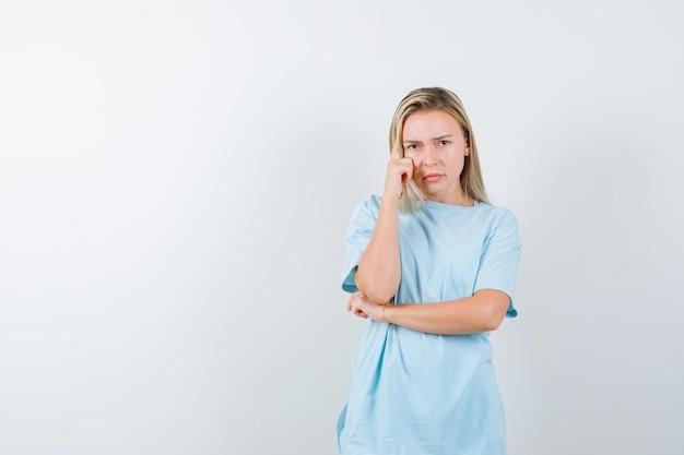 Młoda dama stojąca w myślącej pozie w koszulce i patrząca na zamyśloną odizolowaną