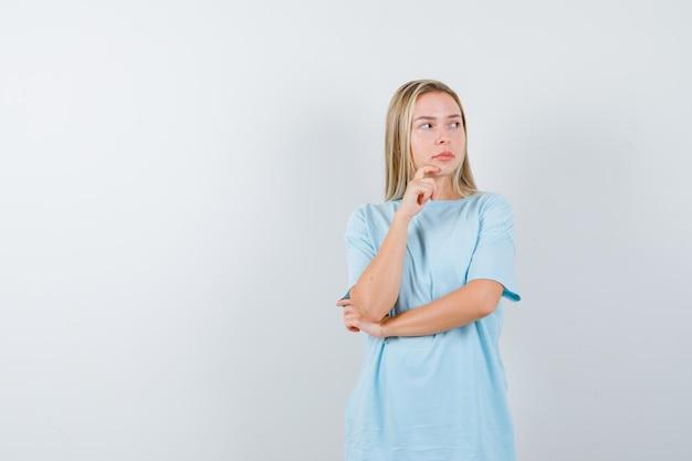 Młoda dama stojąca w myślącej pozie w koszulce i patrząca niezdecydowana odizolowana
