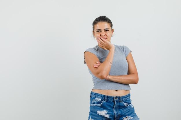 Młoda dama stojąca w myślącej pozie w koszulce, spodenkach i wyglądająca rozsądnie.