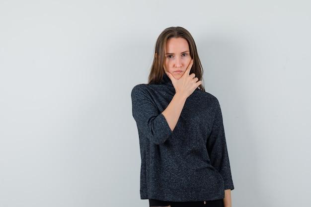 Młoda dama stojąca w myślącej pozie w koszuli i wyglądająca rozsądnie