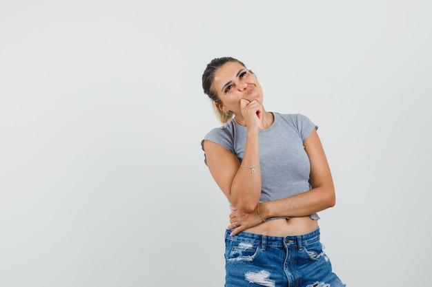 Młoda dama stojąca w myśleniu poza w t-shirt, spodenki