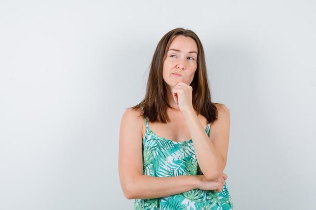 Młoda dama stojąca w pozie myślenia w bluzce i patrząc zamyślony, widok z przodu.
