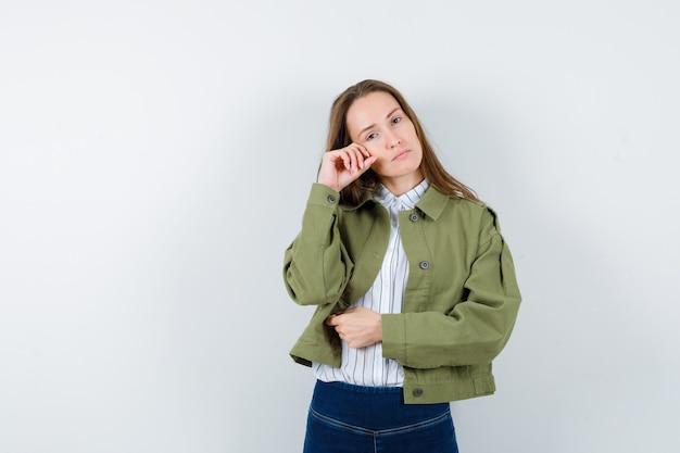 Młoda dama stojąca w pozie myślenia w bluzce, kurtce i patrząc na spokój, widok z przodu.