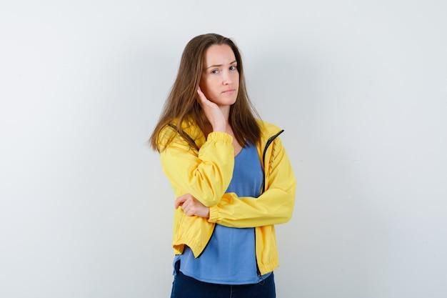Młoda dama stojąca w pozie myślenia w koszulce, kurtce i rozsądnie wyglądającym. przedni widok.
