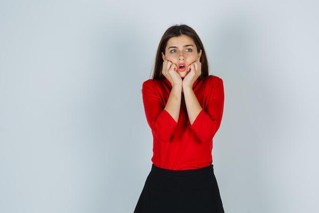 Młoda dama stojąca w przestraszonej pozie w czerwonej bluzce, spódnicy i przerażona
