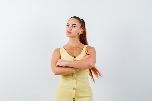 Młoda dama stojąca ze skrzyżowanymi rękami, odwracająca wzrok w żółtej sukience i zamyślona, widok z przodu.