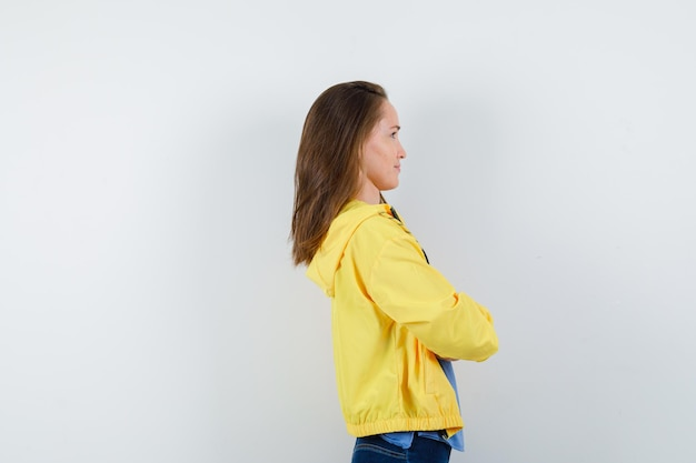 Młoda dama stojąca ze skrzyżowanymi rękami w koszulce, kurtce i zamyślona