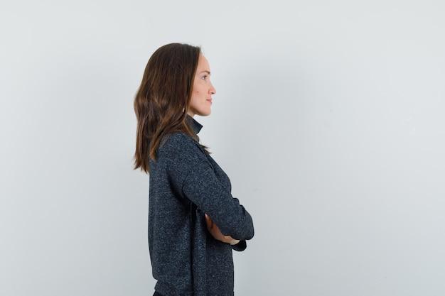 Młoda dama stojąca ze skrzyżowanymi rękami w koszuli i patrząc pozytywnie