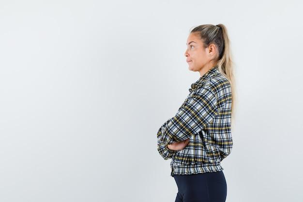 Młoda dama stojąca ze skrzyżowanymi rękami w koszuli w kratkę i zamyślona.