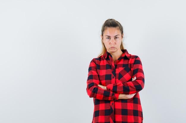 Młoda dama stojąca ze skrzyżowanymi rękami w koszuli w kratkę i zamyślona
