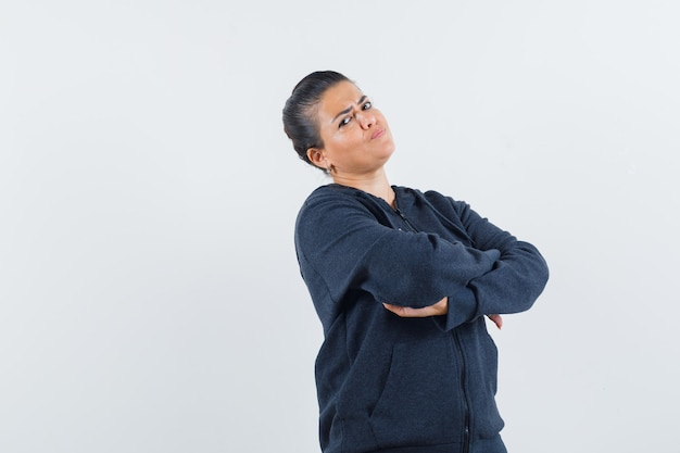 Młoda dama stojąca ze skrzyżowanymi rękami w kurtce i wyglądająca na obrażoną