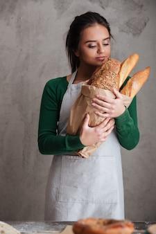Młoda dama szczęśliwy piekarz stojący i trzymając chleb.