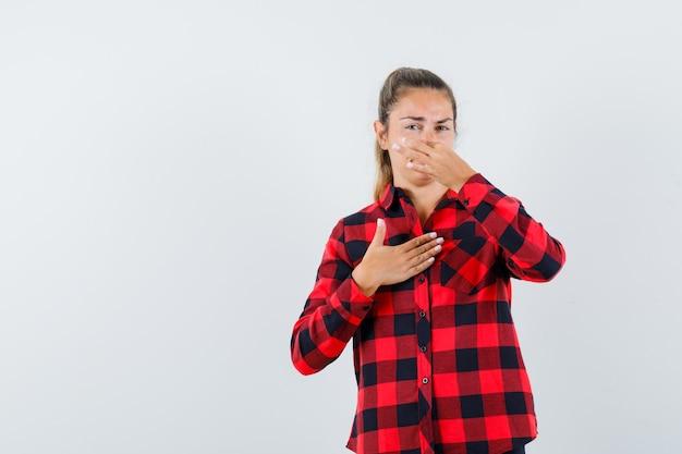 Młoda dama szczypie nos z powodu nieprzyjemnego zapachu w kraciastej koszuli i wygląda na zniesmaczoną