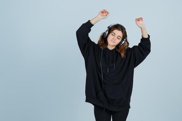 Młoda dama tańczy podczas słuchania muzyki przez słuchawki w obszernej bluzie z kapturem, spodniach i wygląda spokojnie. przedni widok.