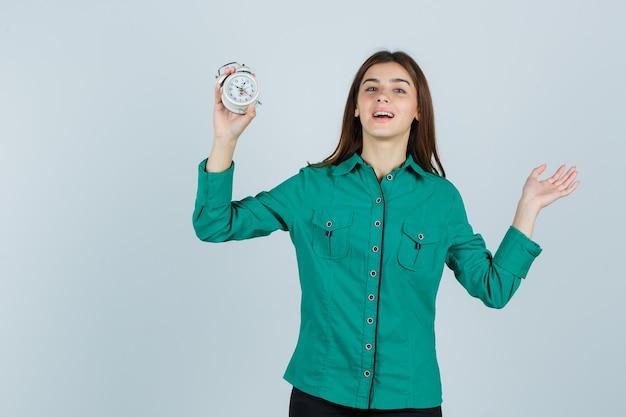 Młoda dama trzyma budzik, pokazując dłoń w koszuli i patrząc wesoło, widok z przodu.