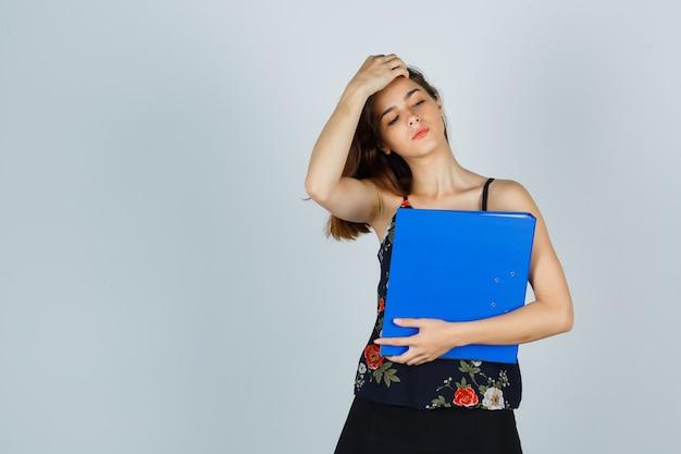 Młoda dama trzyma folder podczas czesania włosów w bluzce, spódnicy i wygląda na zmęczoną. przedni widok.