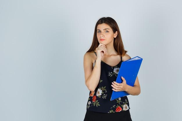 Młoda dama trzyma folder, podpierając podbródek w bluzce i wygląda rozsądnie. przedni widok.