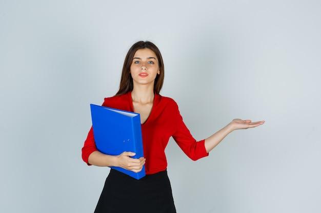 Młoda dama trzyma folder pokazując coś w czerwonej bluzce