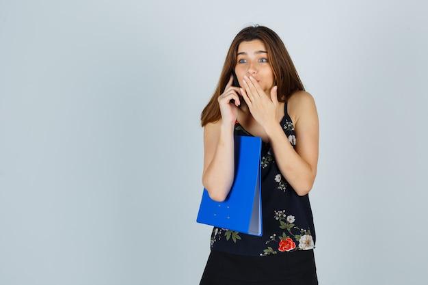 Młoda dama trzyma folder, rozmawia przez telefon komórkowy, trzyma rękę na ustach w bluzce, spódnicy i wygląda na podekscytowaną. przedni widok.
