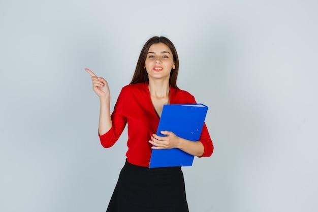 Młoda dama trzyma folder, wskazując na lewy górny róg w czerwonej bluzce